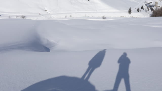 shadow of couple on snow, tilt up to village - lombardia video stock e b–roll