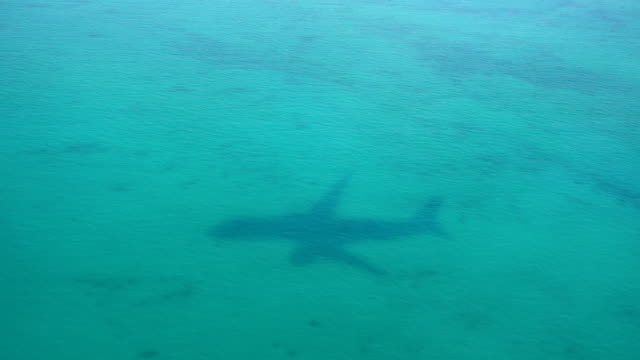 Shadow of the airplane on the sea background