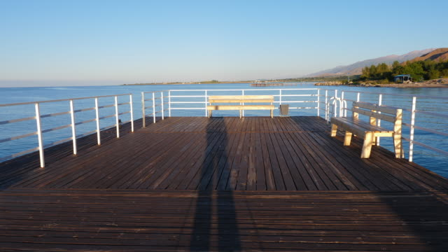 伊塞克湖-伊塞克湖湖長木墩上攝影師的影子 - 亞洲中部 個影片檔及 b 捲影像