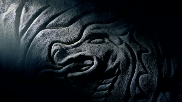 stockvideo's en b-roll-footage met schacht van licht onthult oude draak stone carving - middeleeuws
