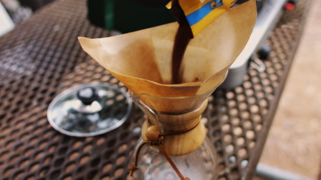 Shaking Coffee into Pour-Over Coffeemaker at Campsite video
