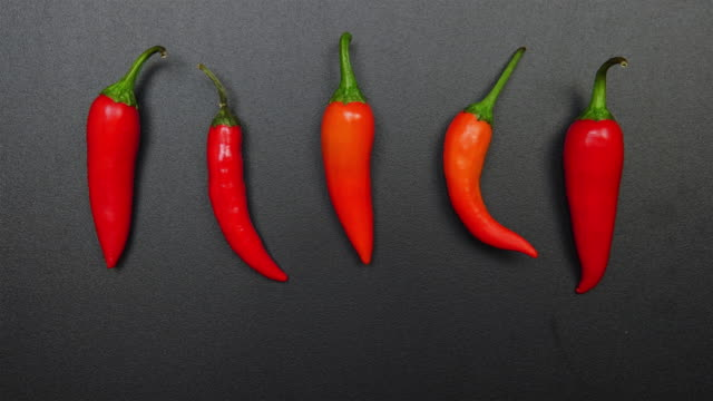 STOP-MOTION: Shaking of a hot peppers on a black table STOP-MOTION: Shaking of a hot peppers on a black table chili pepper stock videos & royalty-free footage