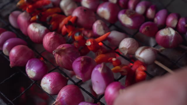 schalottenlök och röd chili på spett få grill på kolgrill. hot fire under. vänd med gamla damen hand. - grillspett bildbanksvideor och videomaterial från bakom kulisserna