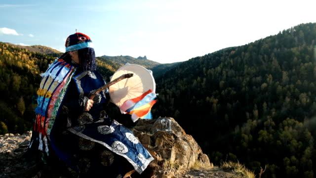 山の上の岩の上に座っているタンバリンをシャーマンがノックします。 - 各国の観光地点の映像素材/bロール