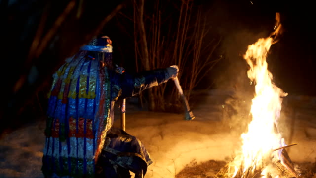 Shamanic ritual by the fire. Shaman shakes a ritual bell by the fire. 4K, slow motion siberia stock videos & royalty-free footage