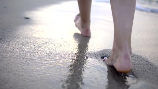 mexico.travelコンセプトのカリブ海の澄んだ水の中でビーチを歩く赤い爪を持つ形の女性の脚。休暇 - 叙情的な内容点の映像素材/bロール