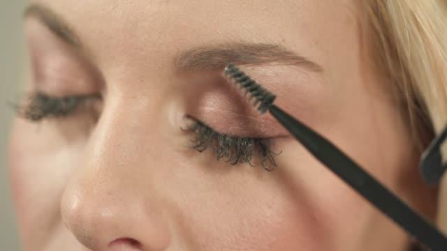 stockvideo's en b-roll-footage met het vormgeven van wenkbrauwen met wenkbrauw kam en potlood - eyeliner