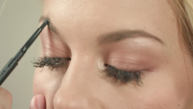 Shaping eyebrows with pencil and brow comb
