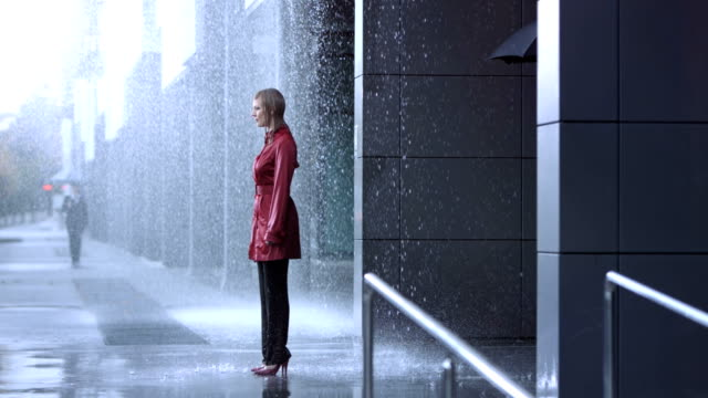 Sharing An Umbrella HD1080p: Slow Motion shot of a businesswoman in a red coat standing all wet in the rain while her colleague surprise her with an umbrella. After covering her under his umbrella,  she give him a warm hug. suit videos stock videos & royalty-free footage