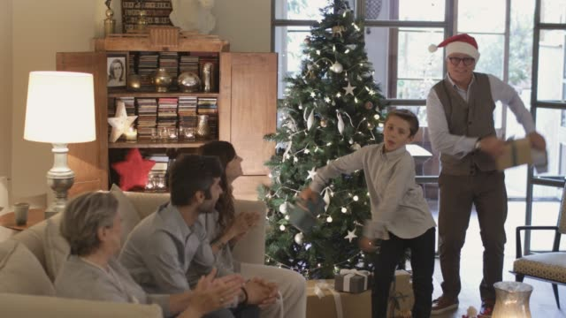 vídeos de stock e filmes b-roll de sharing and opening christmas presents wile dancing the floss dance. - family christmas