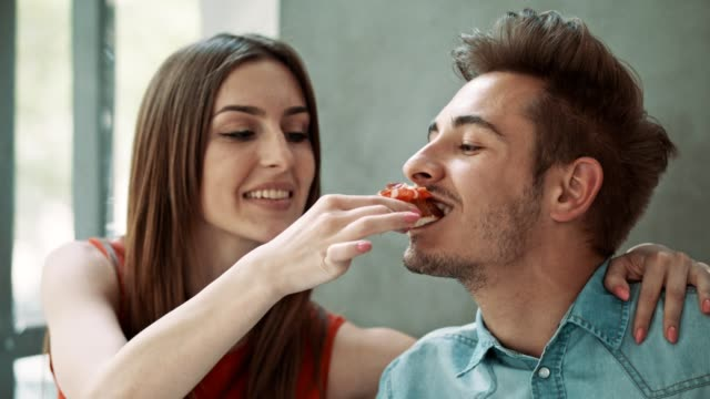 Sharing food Young, in love, couple sharing food and smiling at date lunch. Enjoying their time together. falling in love stock videos & royalty-free footage