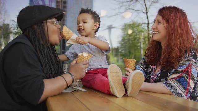 Sharing Ice Cream with Mom A homosexual biracial female couple takes their son out for ice cream. The Son give his mother a taste of his cone. One woman is Caucasian and the other is African-American lesbian stock videos & royalty-free footage