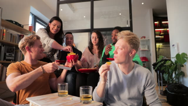Sharing Nacho Chips A front view shot of a multi ethnic group of friends sitting together, they are enjoying snacks and drinks at their home in London, England. They take turns dipping nacho chips into their dips. dipping sauce stock videos & royalty-free footage