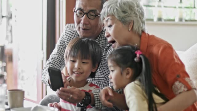 Sharing pictures on mobile phone with the grandchildren Chinese senior couple sharing pictures on mobile phone with the grandchildren at home. east asian ethnicity stock videos & royalty-free footage