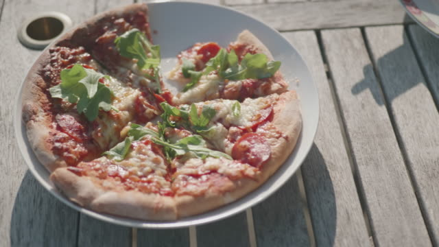 sharing pizza on plate in summer garden