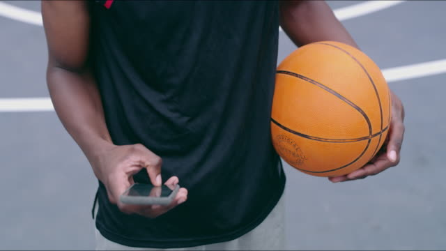 Sharing the game with social media 4k video footage of a man using a smartphone after playing a game of basketball athleticism stock videos & royalty-free footage