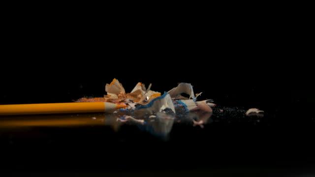 sharpened pencil on a black background. - truciolo video stock e b–roll