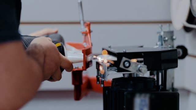 vídeos de stock, filmes e b-roll de afiando um skate no gelo no equipamento, faíscas voam. a lâmina de um skate de gelo é afiada em uma ferramenta de máquina. em um close-up. - afiado