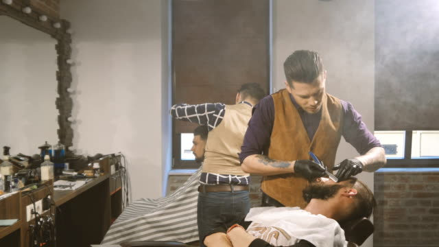 Shaving process of beards in Barbershop. Master makes a haircut beard client with vintage straight razor. video