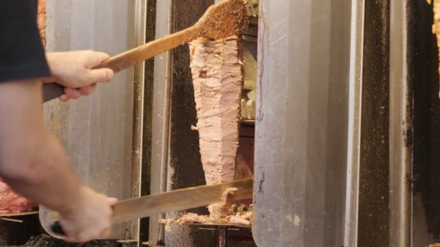 shawarma machine rotating and grilling meat with spices. Shaurma, Turkish doner-kebab. Fast street food. Chef prepares shaurma doner, stacked meat roasting.