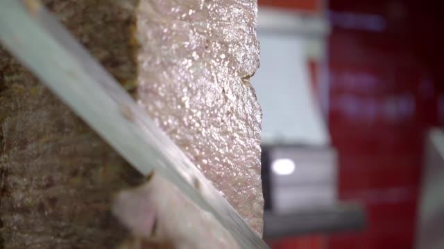 Shawarma meat being cut before making traditional Turkish Doner Kebab