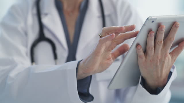 She always has a digital assistant at hand 4k video footage of an unrecognisable doctor using a digital tablet general practitioner stock videos & royalty-free footage
