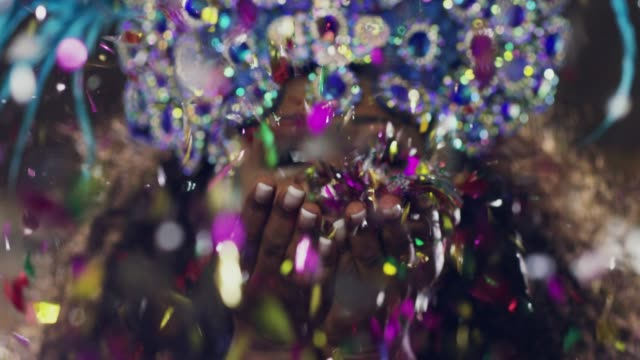 She brings the festive cheer Shot of an attractive cheerful woman wearing festive clothing blowing glitter and confetti at the camera inside of a small club at night carnival celebration event stock videos & royalty-free footage