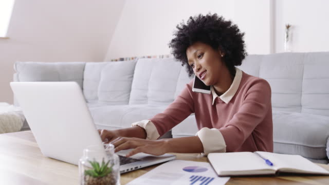 She gets more work done in half the time 4k footage of an attractive young woman using a laptop and mobile phone while working at home black people stock videos & royalty-free footage