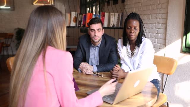 vídeos y material grabado en eventos de stock de ella les ayuda a tomar decisiones inteligentes con su dinero mientras presentan soluciones en su computadora portátil - planificación financiera