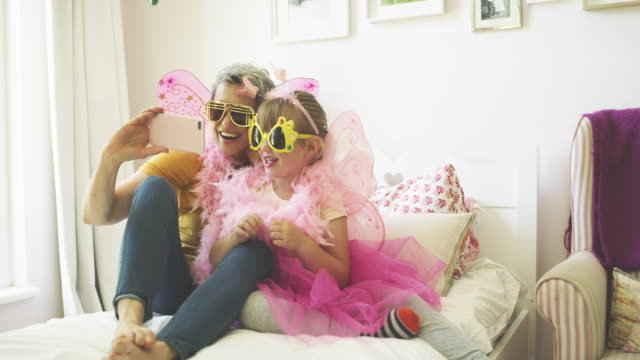 She inherited my sense of humor 4k video footage of a grandmother taking selfies with a cellphone while playing dress up with her granddaughter at home dressing up stock videos & royalty-free footage