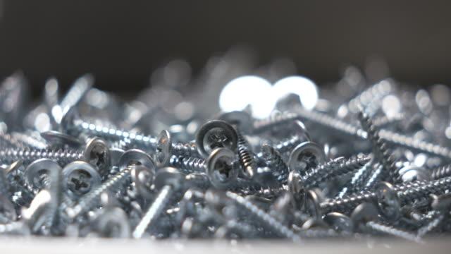 Sheet metal screw background. Pile of self-tapping screws rotation.