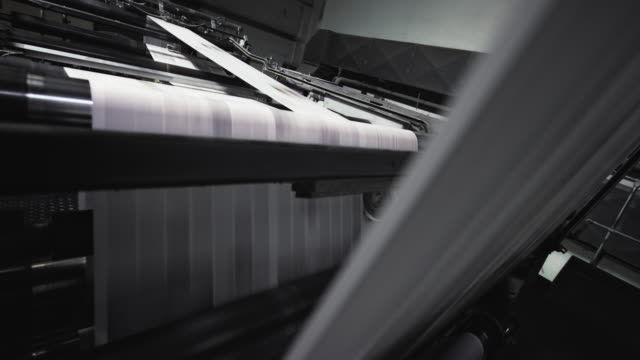 sheets of paper running across the rolls of the printing press - newspaper paper video stock e b–roll