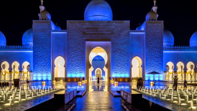 vídeos de stock, filmes e b-roll de mesquita sheikh zayed grand iluminada à noite timelapse, abu dhabi, emirados árabes unidos - característica arquitetônica