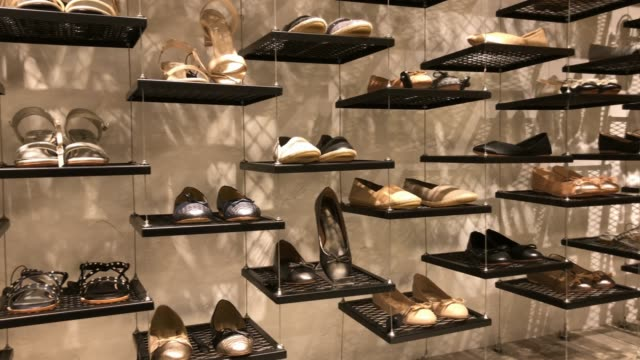 shelf of shoes in retail store at shopping mall - личный аксессуар стоковые видео и кадры b-roll