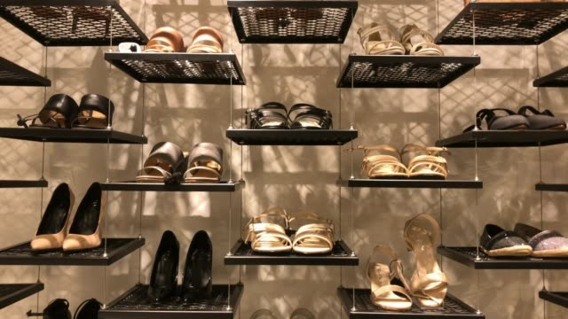 shelf of shoes in retail store at shopping mall - borsa della spesa video stock e b–roll