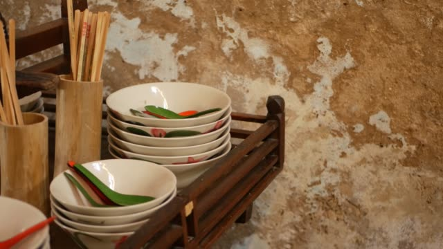 Shelf with oriental dishware. Wooden shelf with various Asian dishware hanging near crumbling wall in kitchen.