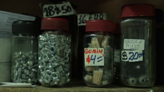 shelf with screw jars and nails in the hardware store. close-up. - винт стоковые видео и кадры b-roll