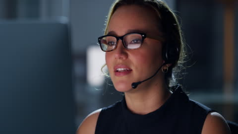 She'll handle your call whatever the hour 4k video footage of a young woman using a computer and headset at night in a modern office service stock videos & royalty-free footage