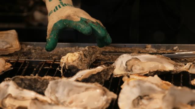 shellfish grilling at seafood restaurant in hiroshima ,japan - hiroshima filmów i materiałów b-roll