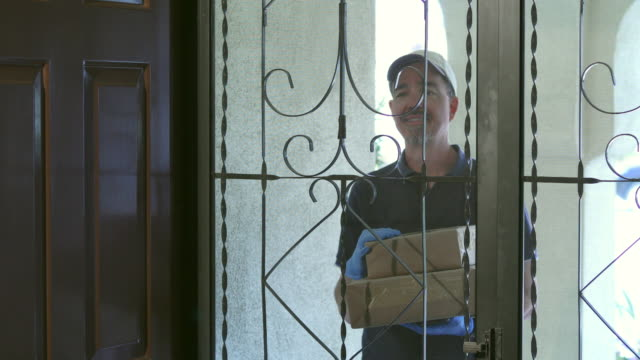 covid-19 shelter at home woman receives package man with gloves - essential workers stock videos & royalty-free footage