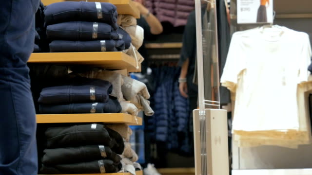 Shelves with clothes in retail store video