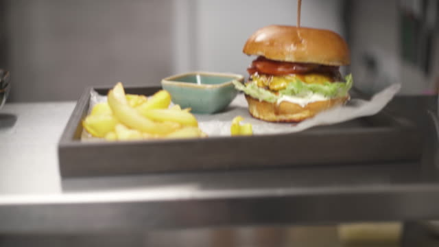 shelves with plates and buns on them. the camera moves bottom up and stops at the upper shelf and a tray with a burger, french fries and a sauceboat with red sauce - taca filmów i materiałów b-roll