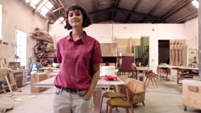 She's a skilled furniture designer 4k video footage of a smiling young woman standing in a furniture manufacturing workshop carpenter stock videos & royalty-free footage