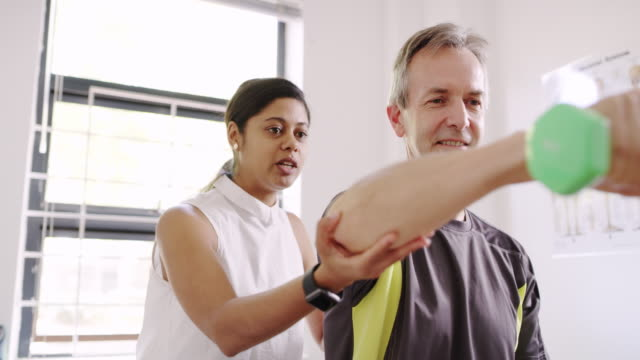 She's hands on! 4k footage of a mature man exercising with dumbbells with the help of a physiotherapist prop stock videos & royalty-free footage