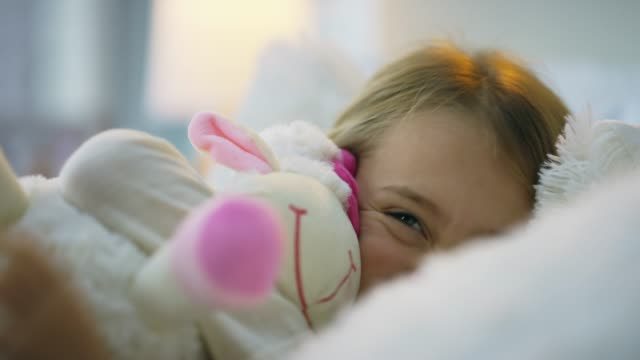 She's simply being her adorable self 4k video footage of an adorable little girl cuddling her teddy bear in bed one girl only stock videos & royalty-free footage