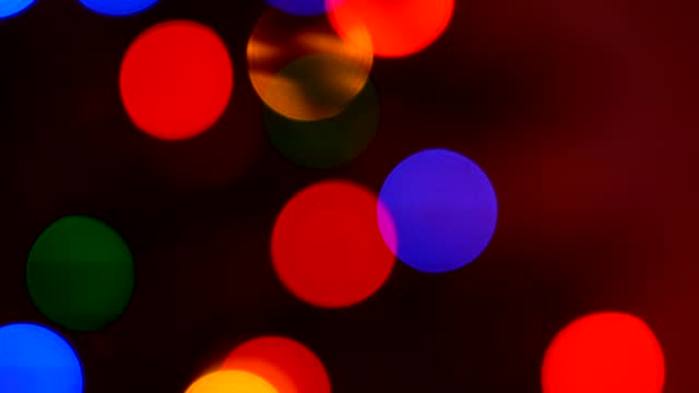 shimmering abstract colored circles defocused christmas lights background. blurred fairy lights. out of focus holiday background christmas tree. light bokeh from xmas tree. xmas and new year theme. 4k video - bokeh stock videos & royalty-free footage