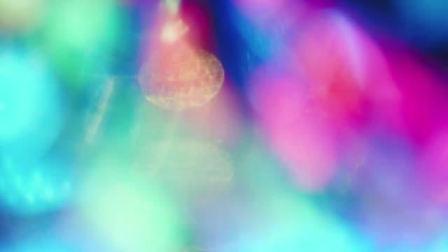 shimmering neon bokeh, iridescent holographic foil. - сюрреалистический стоковые видео и кадры b-roll