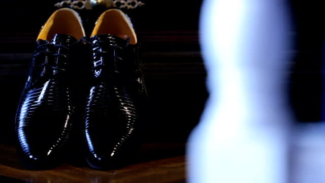 Shining black bridal shoes stand on floor near wooden wardrobe
