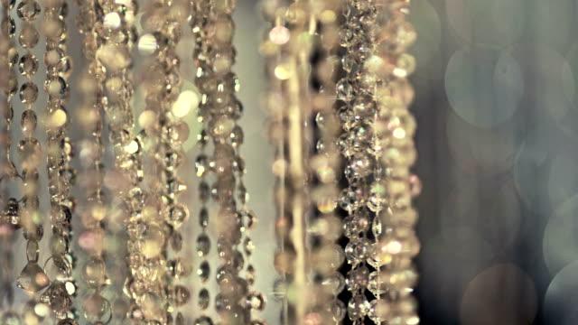parlayan kristal arka plan. kristal bir avize sarkacak. kristal taşlar. ağır çekim. - avize aydınlatma ürünleri stok videoları ve detay görüntü çekimi
