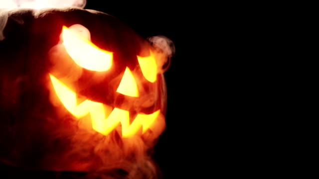 Shining Jack-O-Lantern. Halloween pumpkin with scary face smoke inside with flame isolated on the black background